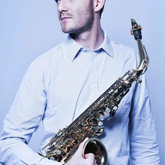 Der Saxophonist Richard Ebert hält sein Saxophon in der Hand und schaut zur Seite