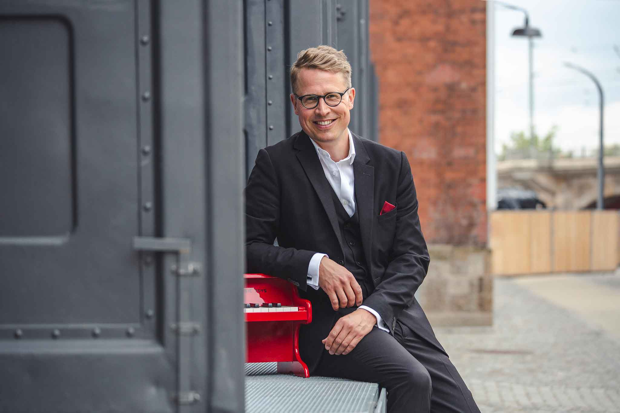 Der Klavierspieler Moritz Töpfer sitzt und stützt sich auf einem Klavier ab.